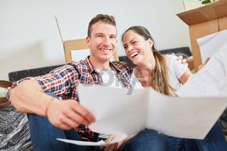 Lachendes junges Paar mit Bauplan