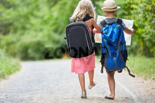 Zwei Kinder mit Rucksack und Landkarte