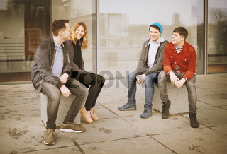 group of young teenage friends talking and laughing together