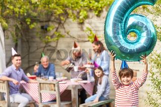 Geburtstagskind hält Luftballon mit der Neun