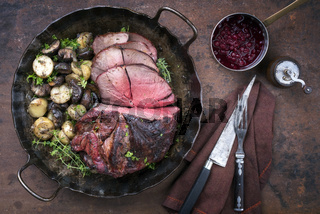 Barbecue dry aged haunch of venison with mushroom and potatoes as close-up on an old cast iron pan