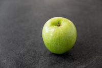 ripe green apple on slate stone background