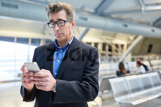 Geschäftsmann staunt über Nachricht auf dem Smartphone