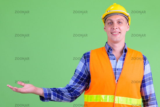 Happy young man construction worker showing something