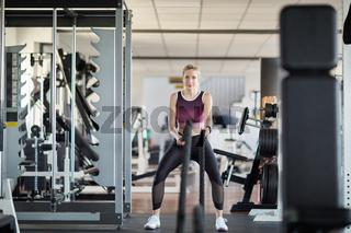Frau trainiert an Battle Rope im Fitnesscenter