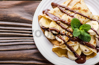 Flat lay French crepes with chocolate sauce and banana in ceramic dish on wooden kitchen table