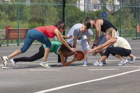 Mixed young team playing basketball on a playground