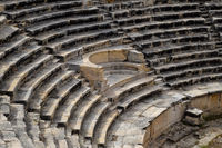 steps of the amphitheater. Stone limestone and marble. Ancient antique amphitheater in city of Hierapolis in Turkey. Steps and antique statues with columns in the amphitheater
