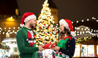 happy couple with gift at christmas market