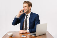 Handsome cheerful blond male entrepreneur sitting in office, calling business partner, contact manager, making order via mobile, smiling relish good deal, drinking coffee, pay online with credit card