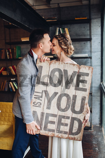 Loving couple kissing holding signboard all you need is love.