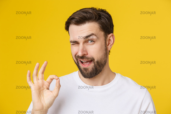 Satisfied young man showing okay sign isolated on yellow background.