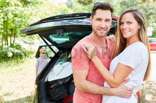 Glückliches Eltern Paar steht vor dem Auto