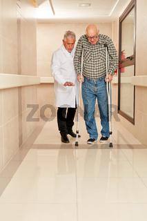 Arzt begleitet Senior Mann auf Krücken