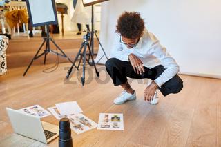 Fotograf betrachtet Fotos für Bildauswahl im Studio