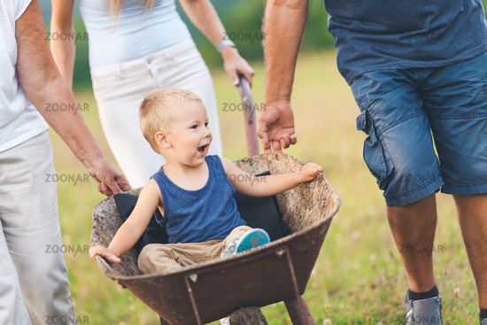 Family pushing their small child and grandchild in a wheelbarrow