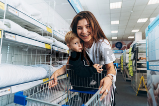 Beautiful mother carries her little son in the supermarket trolley