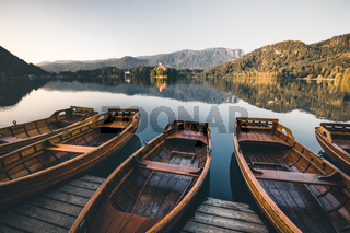 wooden boats at lake bled on a pier in summer during sunrise sunset