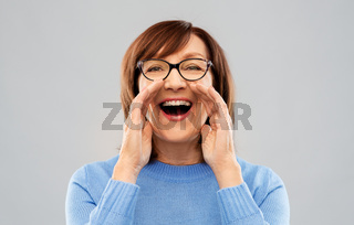 senior woman in glasses calling over grey