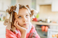 Little thoughtful girl with hair curlers on head