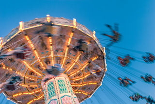 Amusement park motion blurred riders on retro vintage tilting swing against clear blue sky.