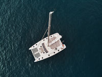 Directly from above view white lonely modern catamaran in calm waters of Atlantic Ocean. Tenerife, Canary Islands, Spain. Concept of lifestyle, adventure activity, beautiful nature and freedom