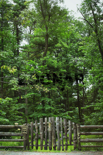 Country fence and sign with forest in background