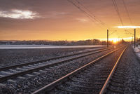 Railway tracks through frozen nature at sunrise. Traveling context. Winter holiday travel.