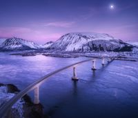 Aerial view of bridge, snow covered mountains, purple sky