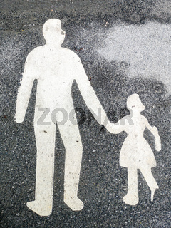 White paint of adult and child walking hand in hand on black asphalt surface of a footpath.