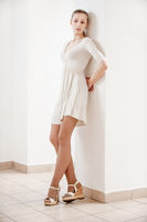 young beautiful woman in white dress leaning on the wall