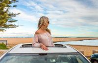 Road trip summer beach vibes.  Carefree woman in sunroof car by beach