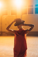 The young, attractive girl in a hat poses to the camera at night