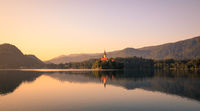 First light of sunrise on silhouette tower of Assumption of Mary church at Lake Bled.