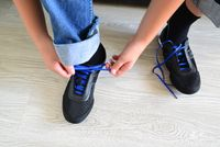 Teenager tying blue laces on the sneakers