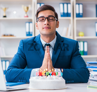 The young businessman celebrating birthday alone in office