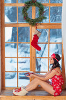 Beautiful young brunette woman wearing red pajamas sitting home by the window