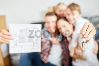 Familie hält Schlüssel als Symbol für Hauskauf