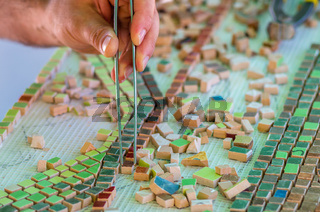 Ceramic design. Ceramic mosaic. The man organizes with a tweezers a puzzle of ceramic elements.