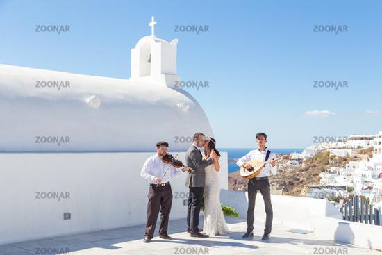 Bride and groom dansing on wedding ceremony on Santorini island, Greece.