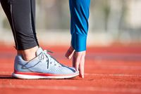Close up view, athlete stretching on a running track.