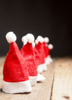 Hats of Santa in a row on rustic wood