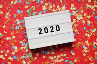 year 2020 lightbox sign on red paper background with confetti
