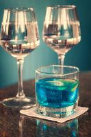Longdrink mit Blue Curacao und zwei Gläser mit Roséwein