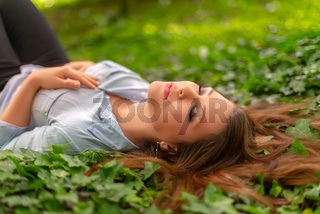 Young beautiful girl with perfect skin and makeup is resting in the park, on spring ivy meadow. Gorgeous woman outdoors enjoying nature. Healthy sleeping beauty lady over a green background