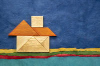 tangram house over abstract paper landscape