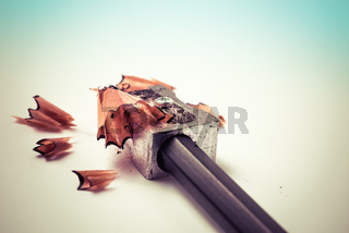 Closeup of sharpening a pencil with a grey metal pencil sharpener with wooden shavings - Concept of school education, learning, student studying, homework or author