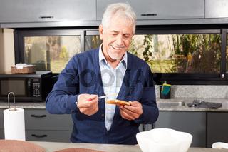 Senior Mann mit einem Toast Brot zum Frühstück