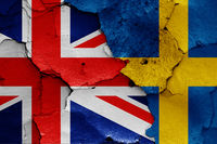 flags of UK and Sweden painted on cracked wall