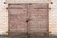 Wooden garage door on brick wall
